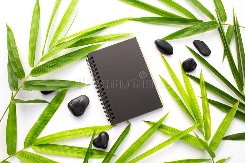 Bamboo leaf zen background. Black paper notebook mockup. Green bamboo leaf and beach pebbles flat lay. Blank page notepad top view. Spa or beauty banner royalty free stock photos