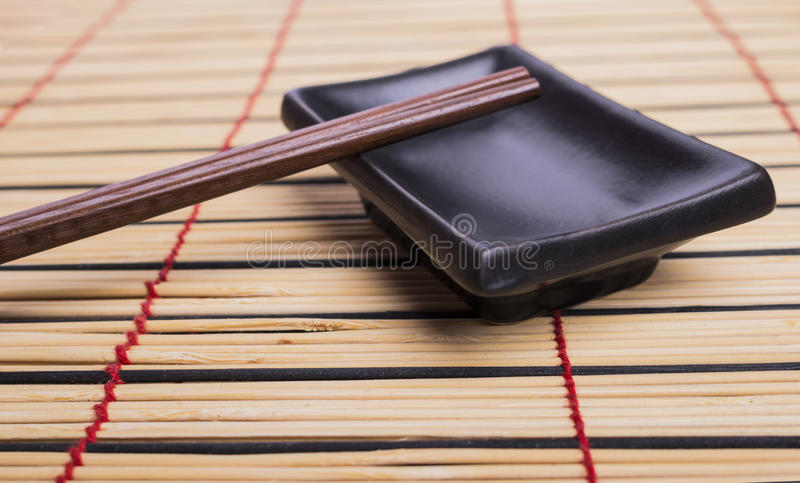 Bamboo mat, dish and chopsticks. On the top royalty free stock image