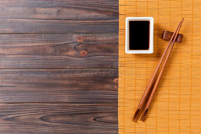 Bamboo mat and soy sauce with sushi chopsticks on wooden table. Top view with copy space background for sushi. Flat lay royalty free stock photo
