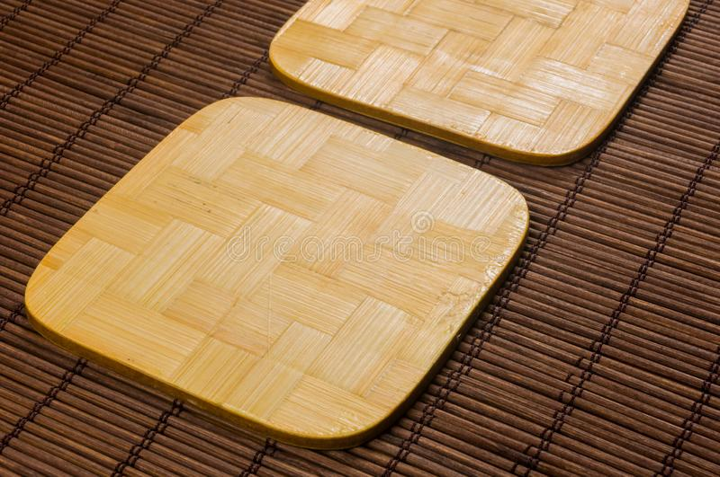 Bamboo Mat - stand food with bamboo stands for hot, close-up, wooden background. Brown bamboo Mat - stand food with bamboo stands for hot, close-up, macro royalty free stock image