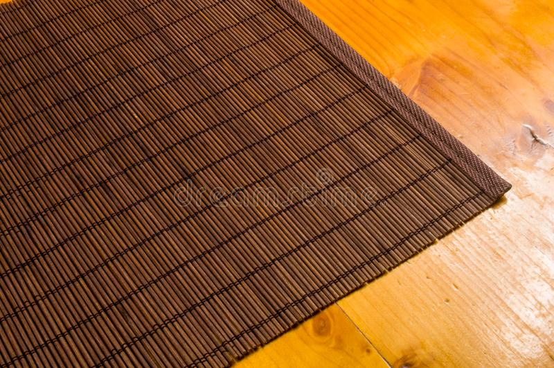 Bamboo Mat - stand food, close-up, wooden background. Brown bamboo Mat - stand food, close-up, macro, wooden background stock images