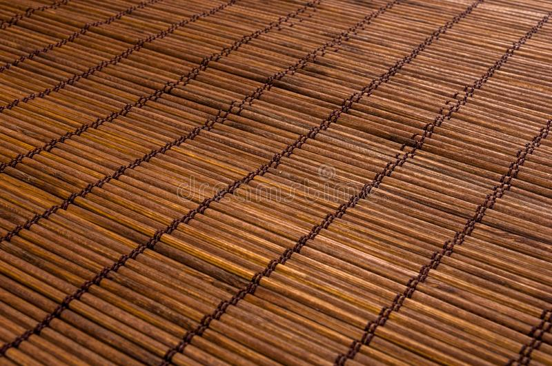 Bamboo Mat - stand food, close-up, wooden background. Brown bamboo Mat - stand food, close-up, macro, wooden background royalty free stock photo
