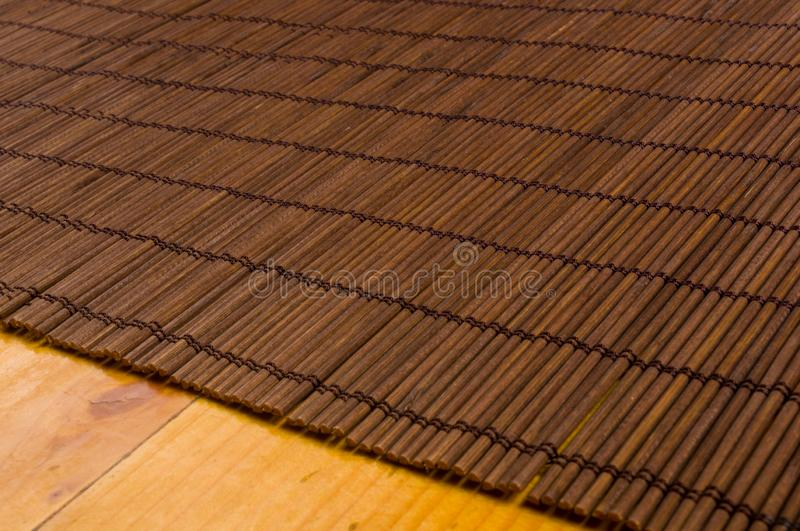 Bamboo Mat - stand food, close-up, wooden background. Brown bamboo Mat - stand food, close-up, macro, wooden background royalty free stock photos