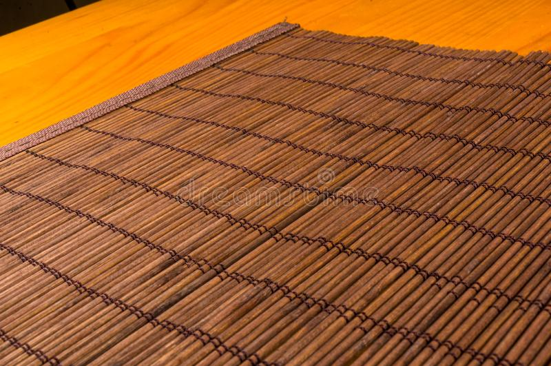 Bamboo Mat - stand food, close-up, wooden background. Brown bamboo Mat - stand food, close-up, macro, wooden background royalty free stock images