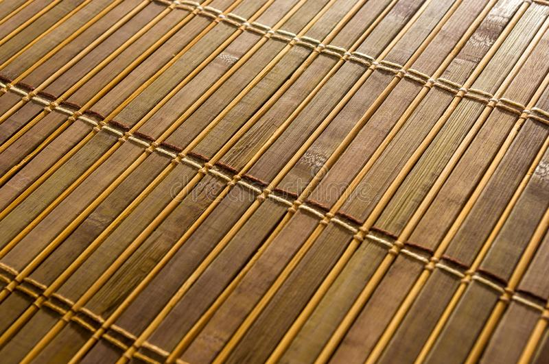 Bamboo Mat - stand food, close-up, wooden background. Brown bamboo Mat - stand food, close-up, macro, wooden background royalty free stock image