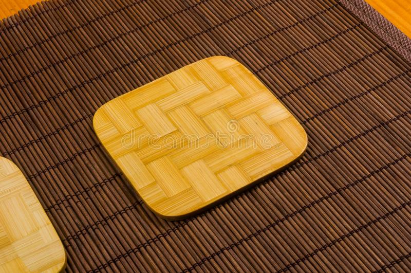 Bamboo Mat - stand food with bamboo stands for hot, close-up, wooden background. Brown bamboo Mat - stand food with bamboo stands for hot, close-up, macro royalty free stock photography