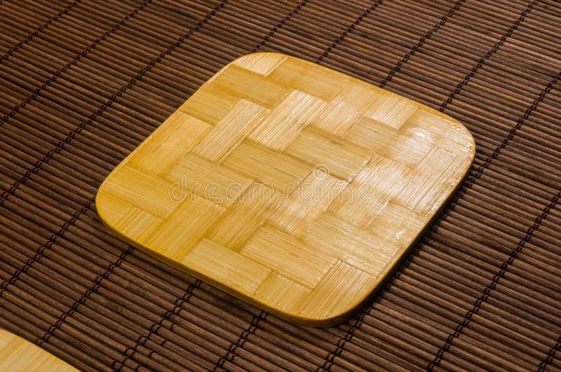 Bamboo Mat - stand food with bamboo stands for hot, close-up, wooden background. Brown bamboo Mat - stand food with bamboo stands for hot, close-up, macro stock photography