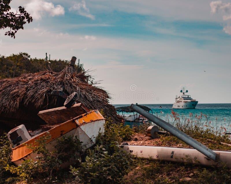 Bamboo paraplyhut och överge båten/skeppet som rostar bort arkivfoto