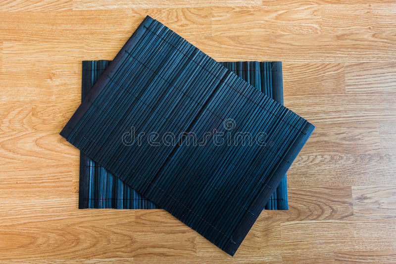 Bamboo placemat straw wood. On wooden background royalty free stock images