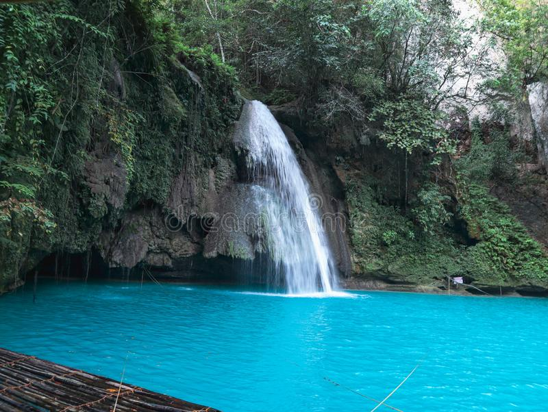 Bamboo raft on turquoise waterfall pool in Kawasan Falls in Cebu Island. Waterfall with bamboo raft on the turquoise water pool at Kawasan Falls in Cebu Island royalty free stock image