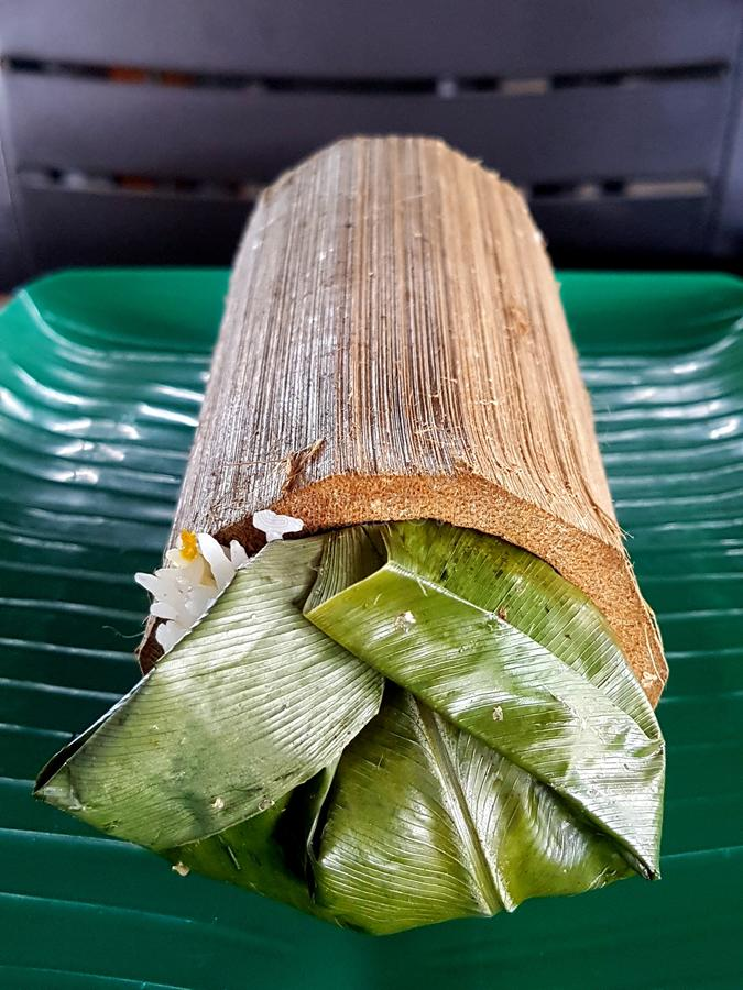 Bamboo Rice. White rice wrapped with green leaf and cooked in bamboo royalty free stock photo