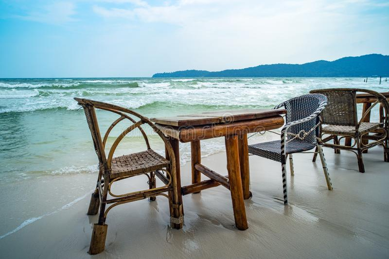 Bamboo table and wooden chairs in empty cafe next to sea water in tropical beach. Close up. Island Koh Phangan royalty free stock photo