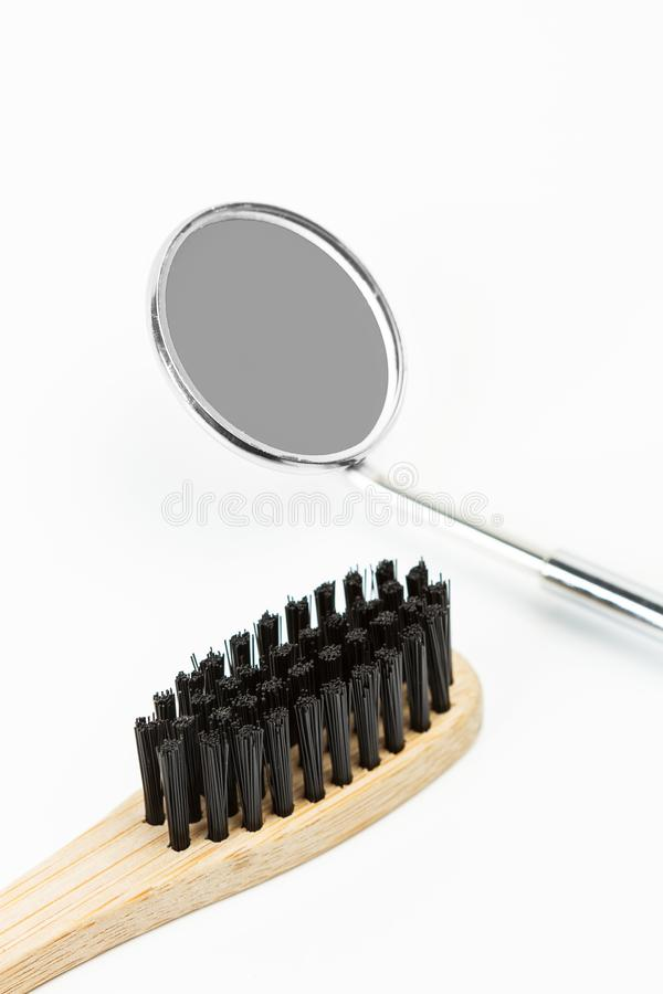 A bamboo toothbrush and a dentist mirror stock photos