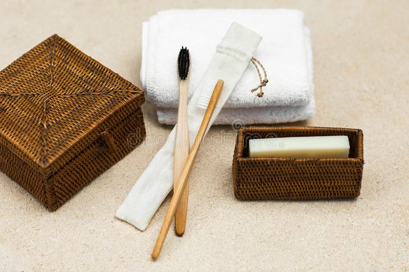 Bamboo toothbrushes and eco soap. Natural bamboo toothbrushes, solid coconut eco soap, cotton towel and rattan boxes on light background. Bathroom essentials stock image