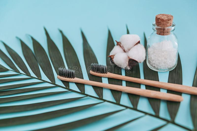 Bamboo toothbrushes, glass bottle with sea salt, cotton flower on palm leaf on blue background. Zero waste concept stock images
