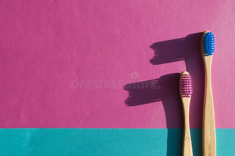Bamboo toothbrushes of magenta and blue color. The most eco-friendly alternative to plastic. Trendy concept royalty free stock photography