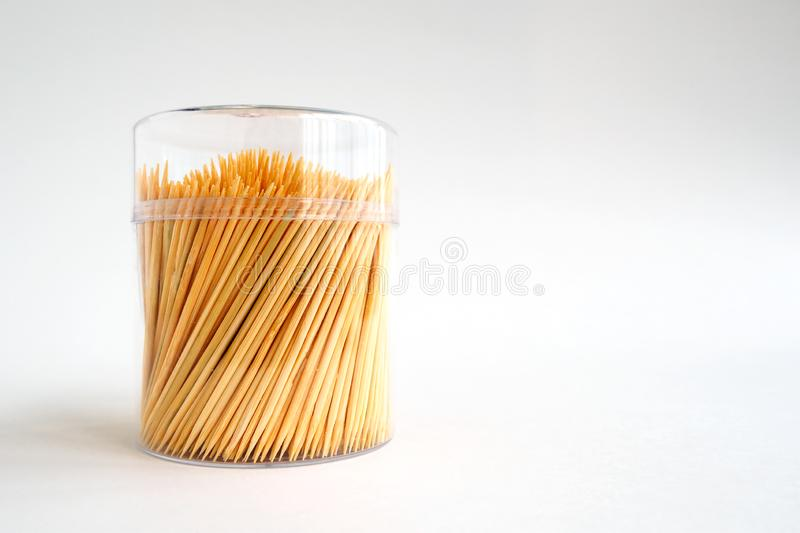 Bamboo toothpicks in a plastic lidded storage box on white background, copy space. Bamboo toothpicks in a plastic lidded storage box on white background, copy stock photography