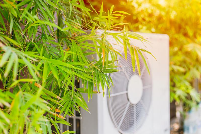 Bamboo tree with air compressor. For cooling home with nature to protect global warming concept stock photography