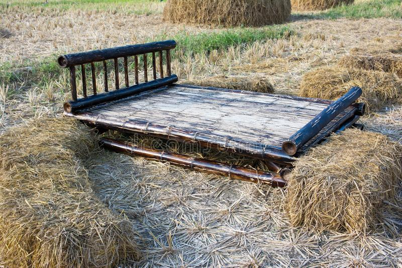 Bamboo wood bed at rice field background. Brown bamboo wood bed at rice field background royalty free stock photo