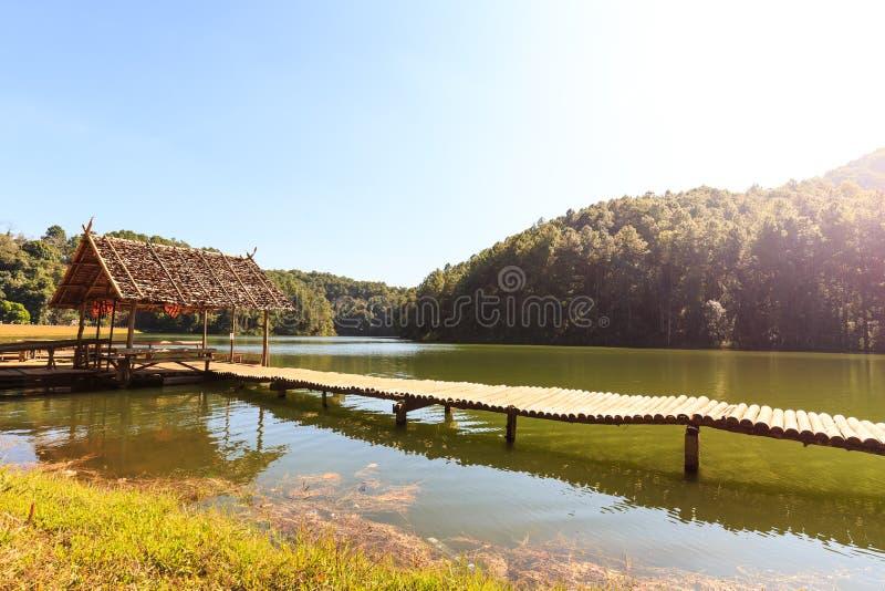 Bambubro och koja i sjön och campa plats arkivbilder