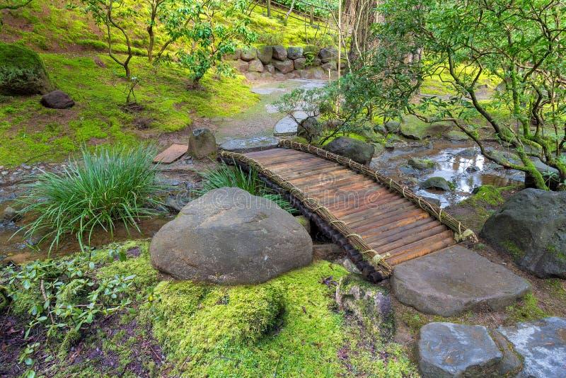 Bambufotbro över liten vik royaltyfri fotografi
