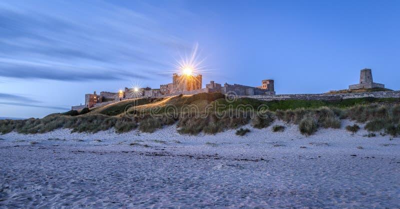 Bamburgh城堡在从海滩的黎明 免版税库存照片