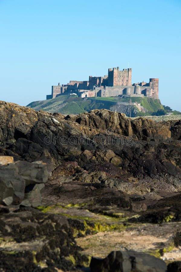 Bamburgh Castle. Viewed across rockpools stock image