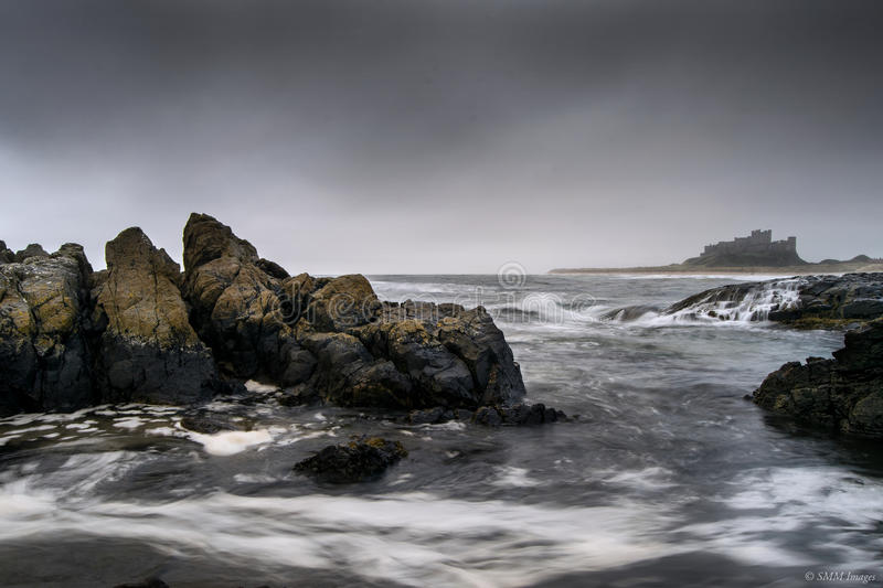 Bamburgh Castle. Image captured during stormy conditions on Bamburgh Beach during the early morning stock images