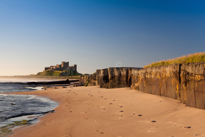Bamburgh Castle, Northumberland, England, Europe. Bamburgh Castle with Rocks. Bamburgh Castle viewed from the beach with rock in the foreground royalty free stock photos