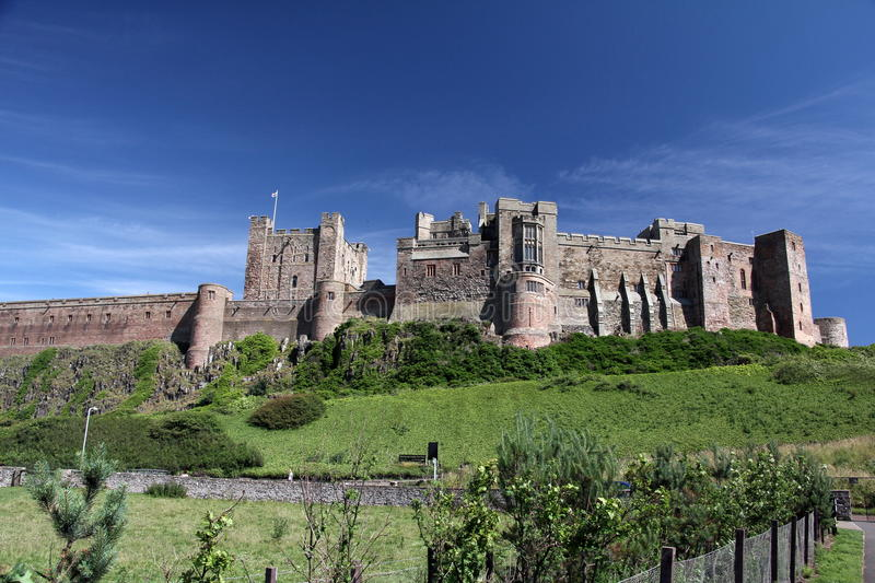 Bamburgh Castle. Sprawling dramatically across nine acres of land, high on it`s rocky perch above the Northumberland coastline, Bamburgh is one of the largest stock images
