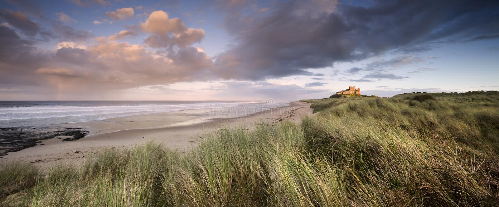 Bamburgh Castle at Sunset. This is Bamburgh Castle in Northumberland, England. The Farne Islands are visible on the horizon. There is a faint rainbow to the left royalty free stock photography