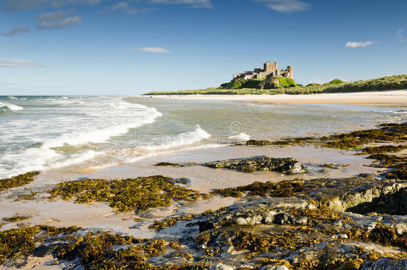 Bamburgh Castle with waves. Bamburgh Castle taken here from the north beach dates back to the 6/7th century royalty free stock image