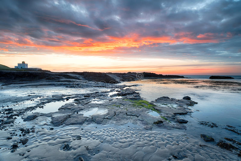 Bamburgh in Northumberland. Sunset over the lighthouse and beach at Bamburgh on the Northumberland coast royalty free stock images