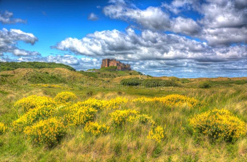 Bamburgh Roszuje Northumberland na wzgórzu z cloudscape w hdr obraz stock