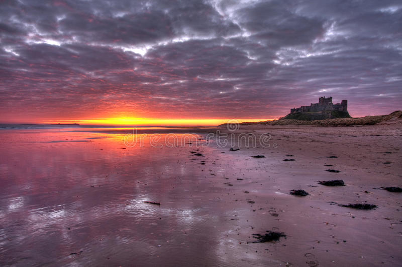 Bamburgh Sunrise. Bamburgh beach and castle at low tide with the Sunrise Northumberland UK royalty free stock images