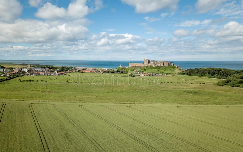 Bamburgh village and Castle, Northumberland, England. An elevated drone view of Bamburgh Village and Castle on a bright summers day with arable farmland in the royalty free stock images