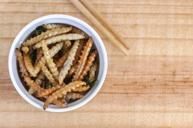 Bambus- essbare Wurminsekten knusperig oder Bambus-Caterpillar in der weißen Schüssel auf einer hölzernen Tabelle Das Konzept von stockbilder