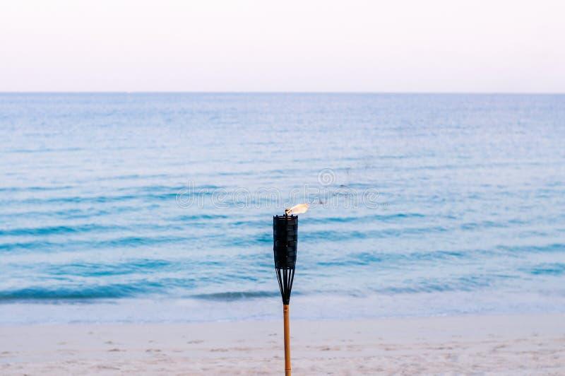 Bambusa ogienia pochodnia na zmierzch tropikalnej plaży - wieczór lata plaży tło obraz stock