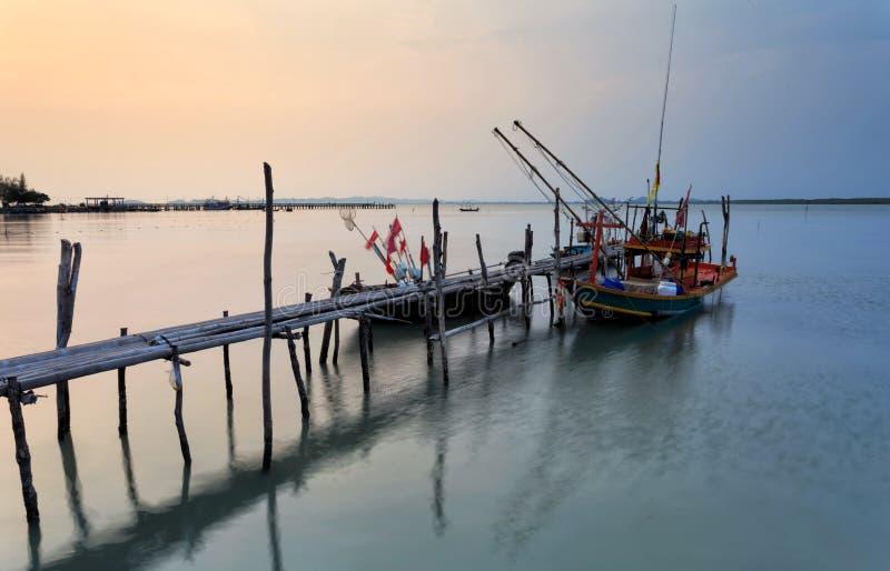 Bambusbrücke und Fischerboot während des Sonnenuntergangs lizenzfreie stockfotos