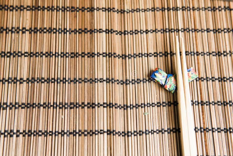 Bambusessstäbchen auf einem handgemachten Origamiessstäbchenhalter stockbild