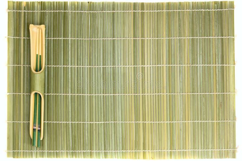 Bambusessstäbchen und Matte lizenzfreies stockbild