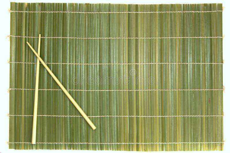Bambusessstäbchen und Matte stockbilder