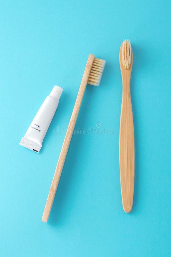 Bambusowi toothbrushes z pastą do zębów na błękitnym tle fotografia stock
