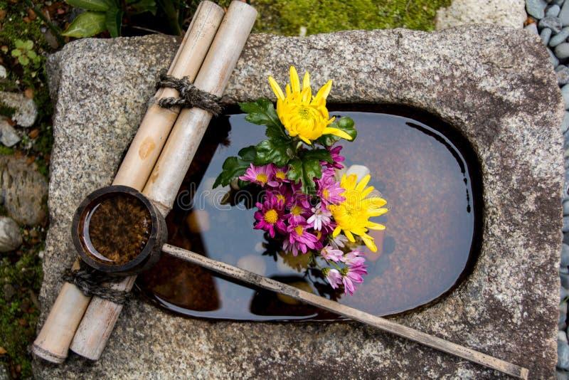Bambusschöpflöffel auf einem Steinbecken füllte mit einer Blumenanordnung in Kyoto Japan stockfotografie