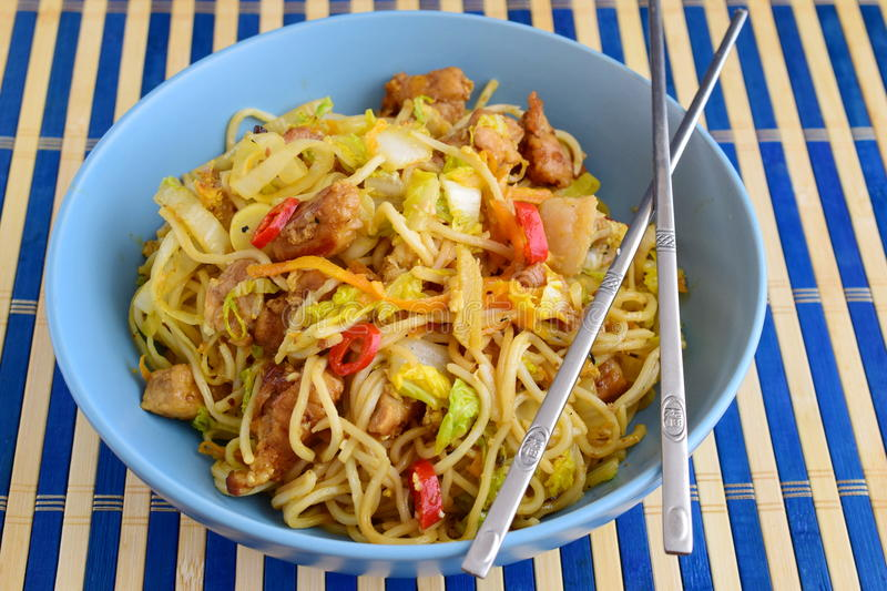 Bami goreng, fried noodles with cabbidge, soja sauce, chili pepper, pork in a blue ceramic bowl on a striped wooden stock photo