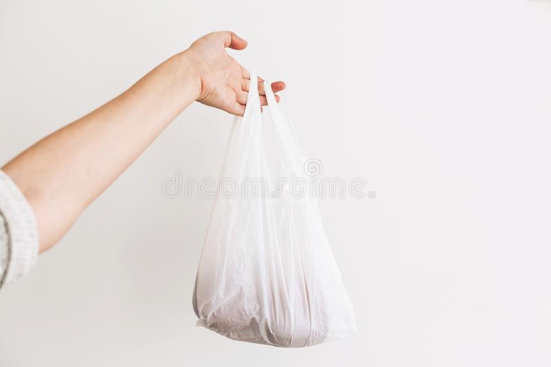 Ban single use plastic. Woman holding in hand groceries in plastic polyethylene bag. Zero Waste shopping concept.  Reuse, reduce, stock images