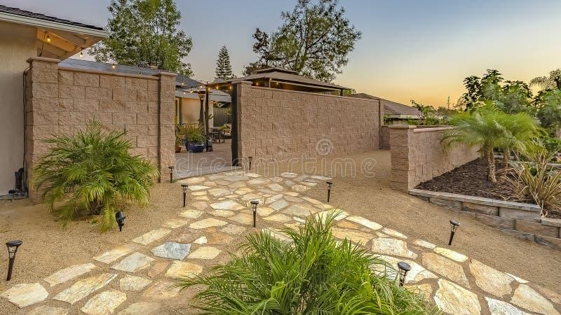 Bana för panoramaramsten som fodras med pollareljus utanför stenstaketet av ett hus arkivbild