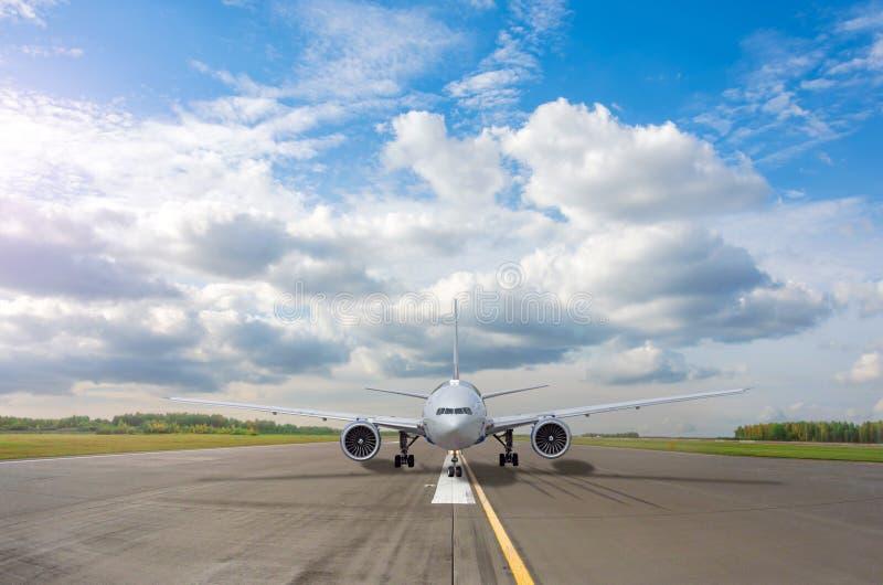 bana med passagerarflygplan redo för start, flygremsa med markering på blå himmel med molnbakgrund Flygresor arkivbild
