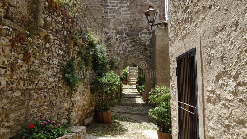 Bana mellan stenväggar och hus i Italien royaltyfri foto