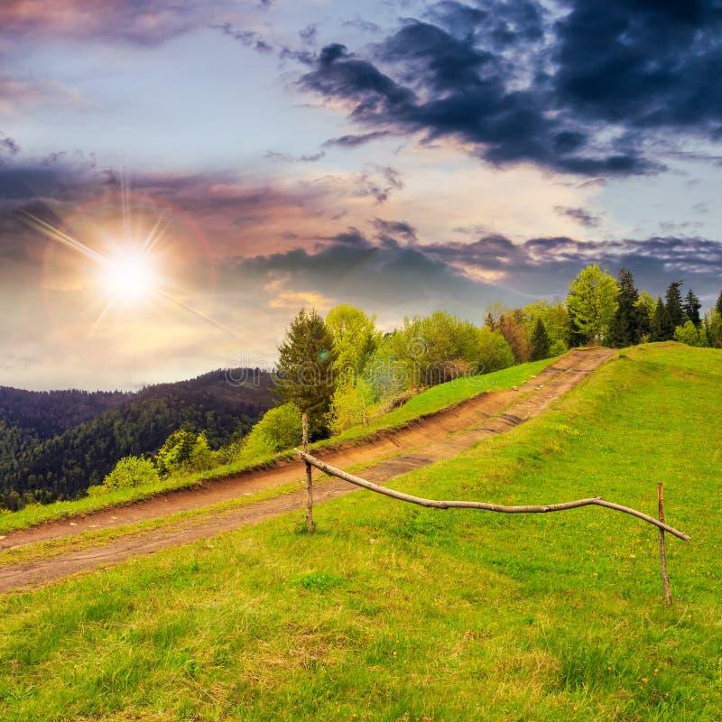 Bana på backeäng i berg på solnedgången royaltyfri fotografi